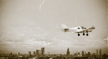 cessna: Vintage image of a personal plane flying over the city Stock Photo