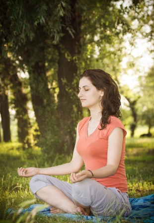 Young women in lotus position trying a breathing exercise in nature photo