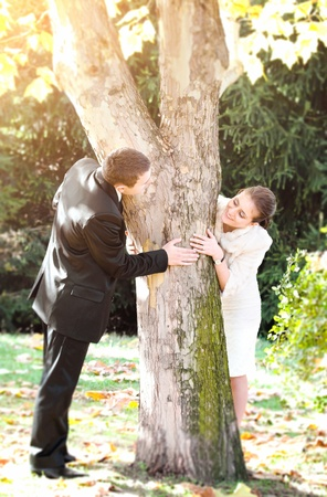 hands holding tree: Young couple playing hide and seek around a tree