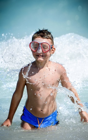 Happy child playing in the black sea photo