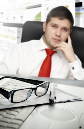 Young businessman at office with selective focus on glasses and pen Stock Photo - 14679883