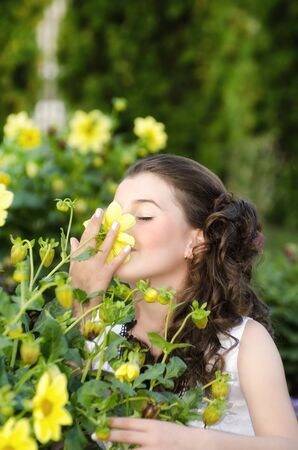 Young little girl holding and smelling a beautiful flower photo