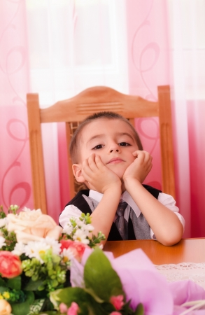 Little boy sitting on chair and thinking Imagens