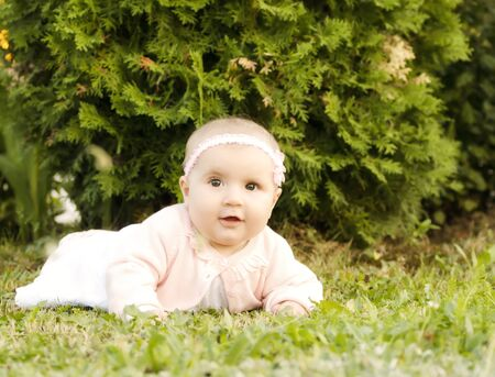 Happy baby girl in the grass looking at camera photo