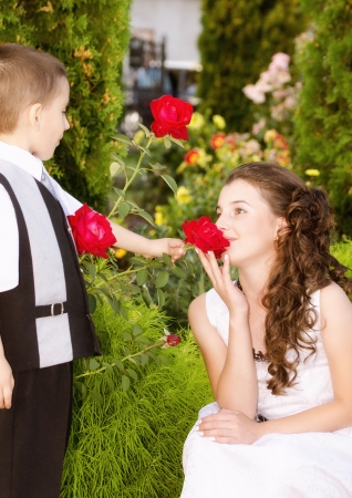 Little boy giving a rose to a beautiful girl photo