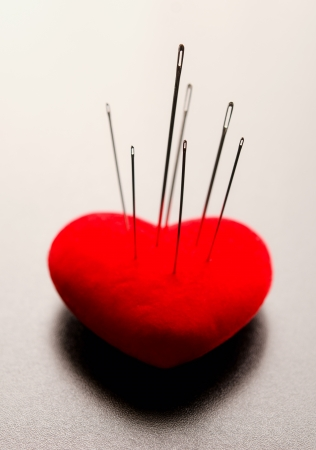 Macro shoot of a red heart Pierced by needles with selective focus on needles Stock Photo