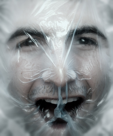 simulate: Young man close up with a plastic bag on his head-NOTE:Soft blur was added to simulate a ghost effect.