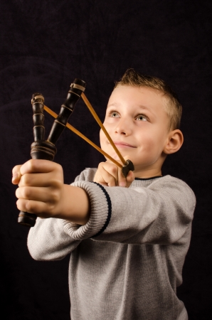 brat: Studio photo of a young boy with slingshot Stock Photo