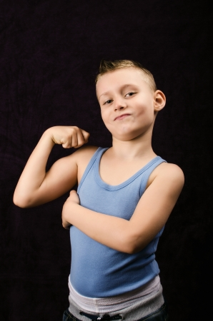 boy muscles: A young boy showing off his muscles on black background Stock Photo