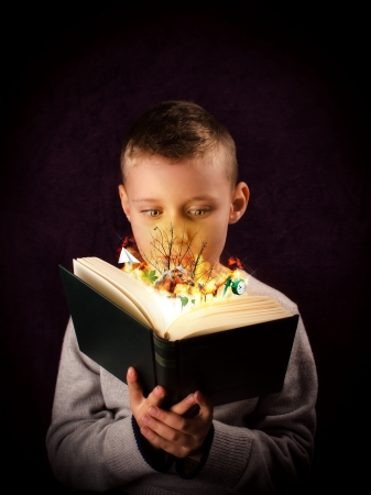 Young boy reading and looking at a magic book photo
