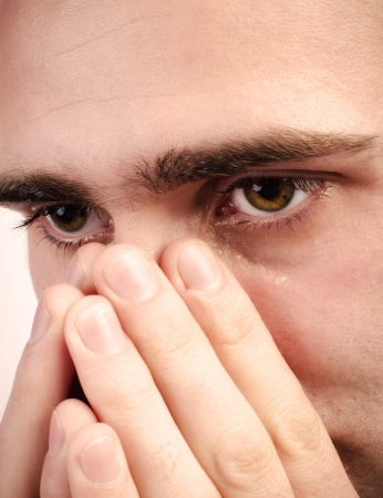Close up of a man crying and a tear is running down a cheek Stock Photo - 16294414