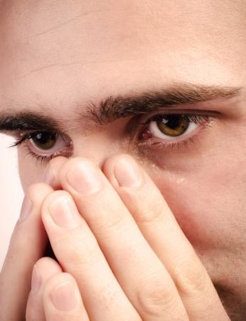 Gros plan d'un homme qui pleure, une larme coule sur sa joue