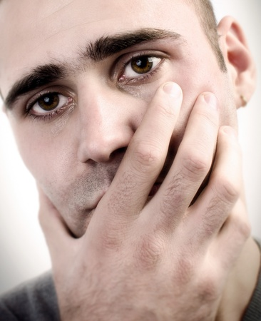 Young man holding his hand on his mouth as an act of depression photo