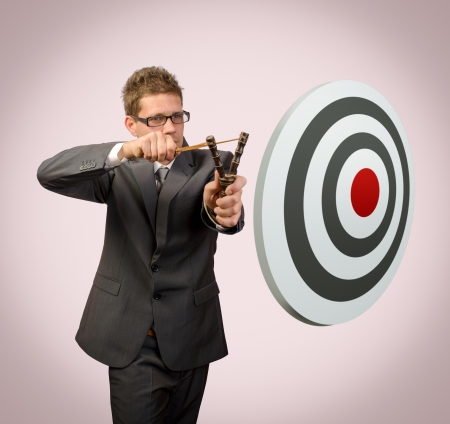 Businessman with slingshoot aiming target Stock Photo - 16546651