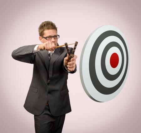 hombre disparando: Hombre de negocios con el objetivo de destino slingshoot