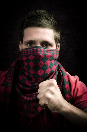 Dangerous hooligan with covered face showing a fist Stock Photo - 16546649