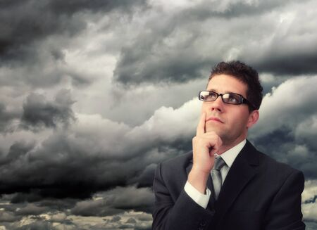 Young businessman against a stormy cloud thinking.Plenty of copy space Stock Photo - 16824340