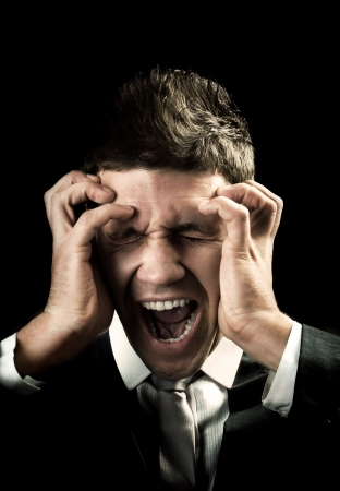 man screaming: Businessman screaming and has a bad headache Stock Photo