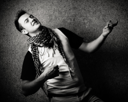 air guitar: Black and white image of a young man playing on a  invisible guitar.High contrast and grain was added Stock Photo