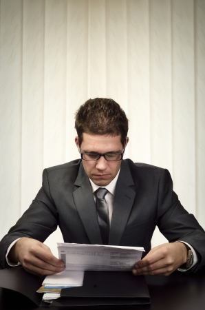 Businessman sitting in his office  attentively reading some document. Stock Photo - 17825157