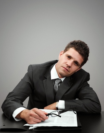 Young businessman tired of paperwork looking at camera Stock Photo - 17857497