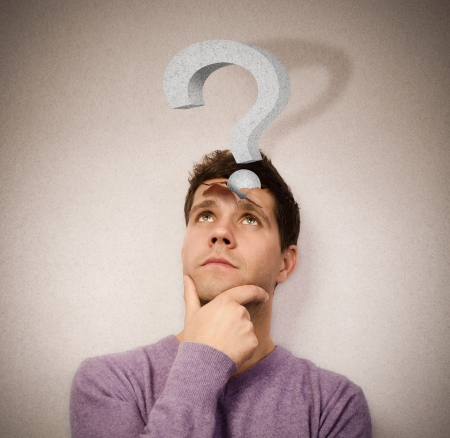 Young man lost in thought with a question mark leaving the head photo