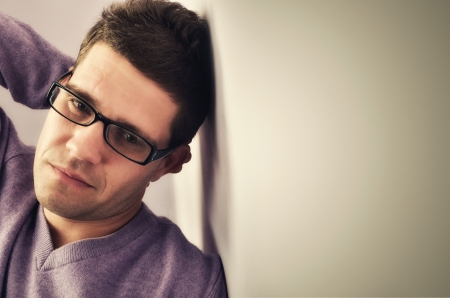 distraught: Young man lost in thought against a wall background