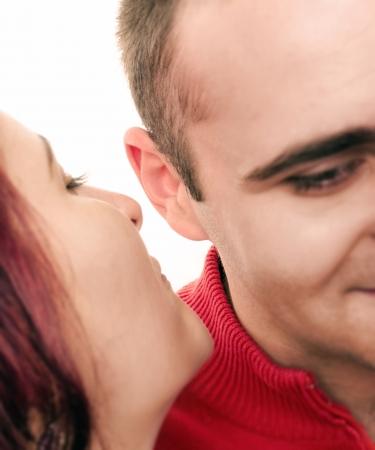 Women sharing a secret to a men Focus on the ear photo