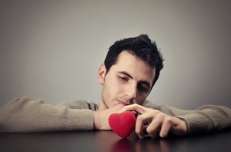 consoling: Young man looking at a heart with a sad look