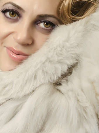 Close up of a beautiful women wearing a fur coat and looking at camera photo