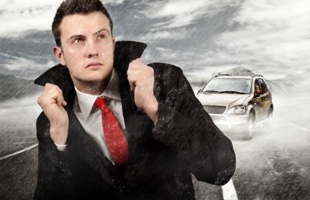 Businessman walking trough the rain after car failure