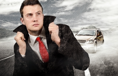 Businessman walking trough the rain after car failure  Stock Photo - 20231013