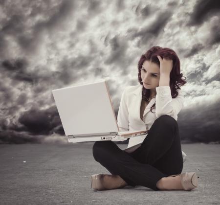 좌절 된 젊은 여성이 바닥에 앉아 컴퓨터를보고