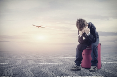 Upsaid boy sitting on baggagebecause he losing the plane Stock Photo - 23572409
