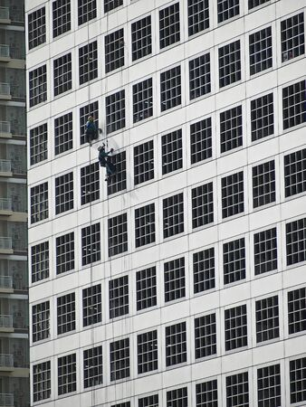 two worker  climb for cleaning outside high building Stock Photo