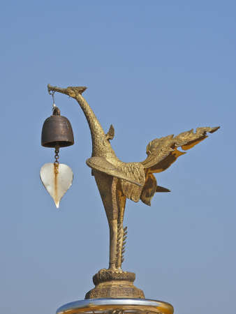 side of golden swan model in the blue sky