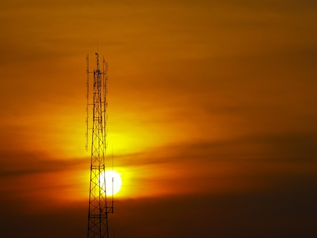 high antenna tower in sunset with orange sky Stock Photo