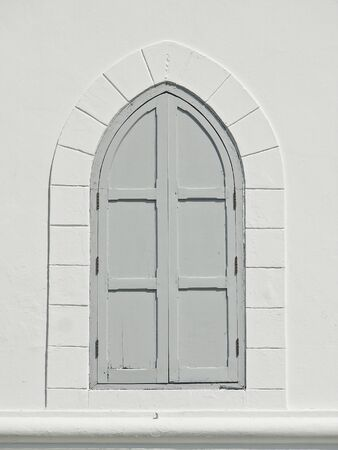 grey window on white wall of fort in sunlight Stock Photo