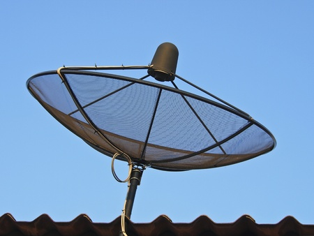 black satellite dish on roof in sunlight Stock Photo
