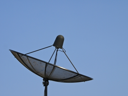 black satellite dish in blue sky and sunlight Stock Photo