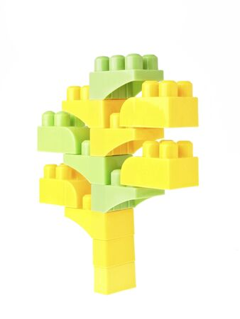 yellow block: green and yellow block toy in tree figure on white background Stock Photo