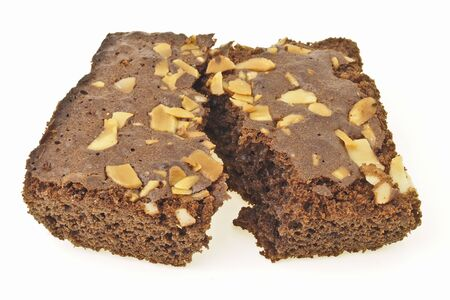 piece of almonds brownies cake split up on white background