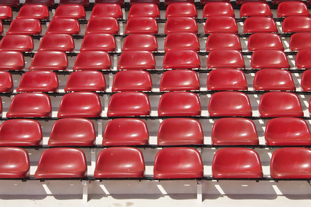 amphitheater of red seats abstract background in sunlight photo