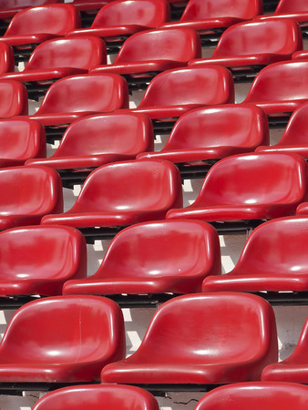 pattern of empty red stadium seats in sunlight photo