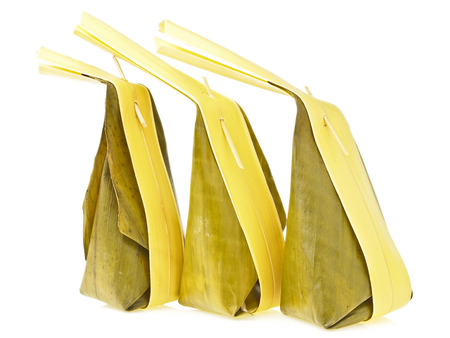 arrange of three banana leaves package with long coconut leaves tail of Thai dessert on white  photo