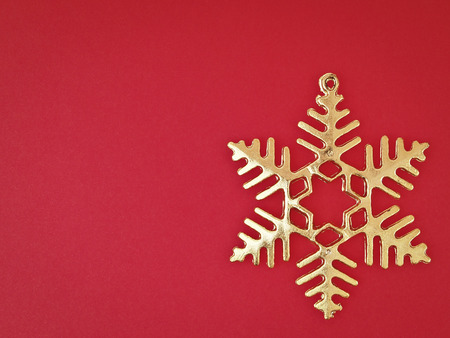 ornament gold snowflake on red background with copy space Stock Photo
