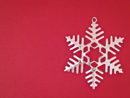 sliver: ornament sliver snowflake on red background with copy space