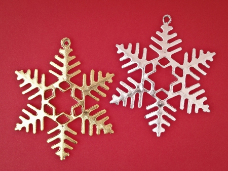 sliver: pair of ornament gold and sliver snowflake on red background