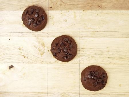 game play: winner cross line pattern of xo game, play by dark brown cookies on wood