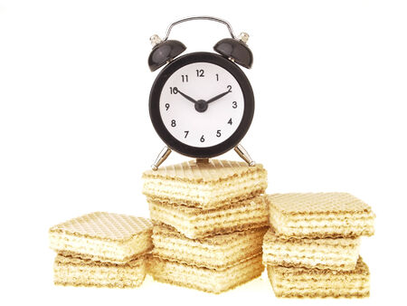 alarm clock on wafer pile isolated on white background photo